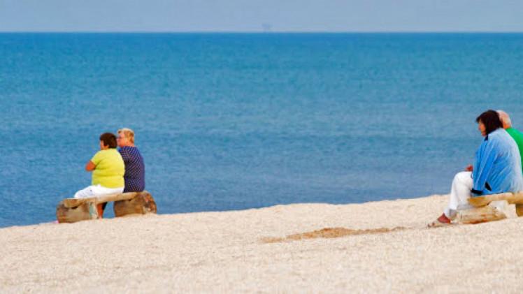 Люди сидять біля моря
